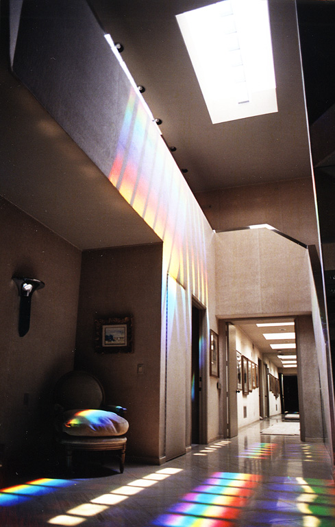 The ceiling skylight is fitted with proprietary flat, laser-cut prisms that refract giant rainbow beams through out the entrance area of this Los Angeles home.