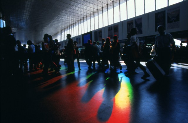 travelers walk through huge rainbow beams in rome termini station