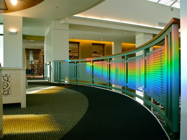 solar powered art projects rainbow onto balcony railing.