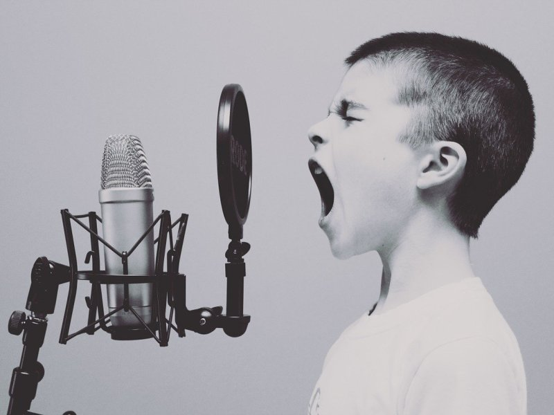 Een kind aan het zingen in de microfoon