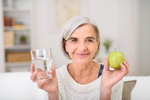 deshidratación en personas mayores anciana sosteniendo un vaso de agua en una mano y una manzana en la otra