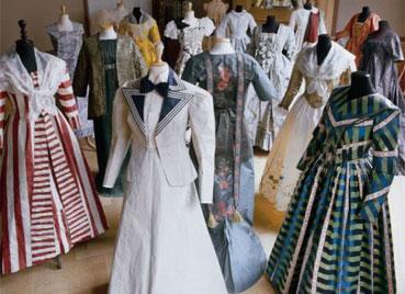 Vestidos e trajes da mostra, que reproduz, em papel, 'new look' da Dior e vestido de Elizabeth 1ª