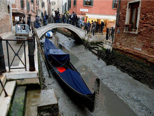 A gondola is seen tied up in Venice, near the Rialto bridge, on January 31, 2018, as exceptionally low tides have drained the lagoon city.