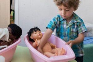 Guardería neutra: Un niño pequeño juega con un muñeco.