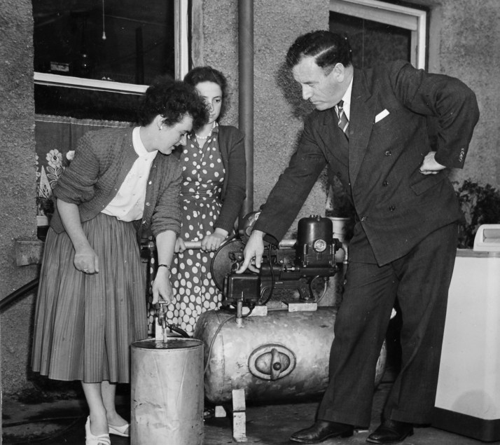 Male demonstrator and two interested housewives, c1960s
