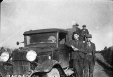 Jerry Corbett leans on the font of the rural electrification van, with his colleagues in the background