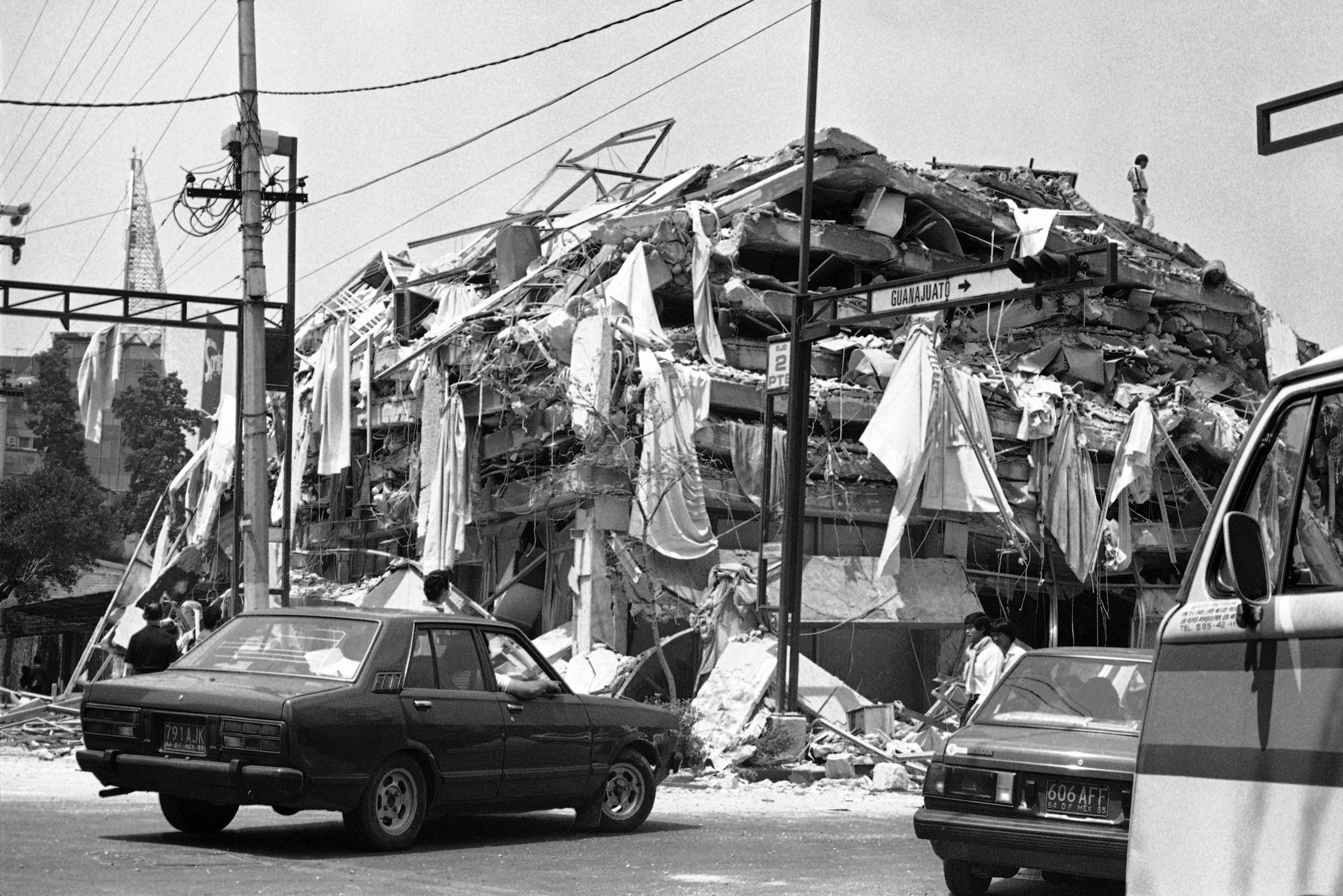 Cars and onlookers pass by a building that is covered with drapery from the windows after it was reduced to rubble after a strong earthquake rumbled through Mexico City, Sept. 20, 1985. (AP Photo/Ed Kolenovsky)
