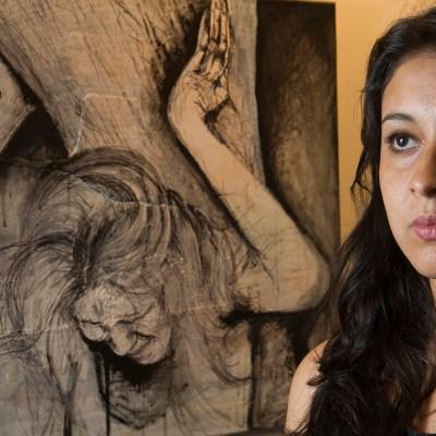 Yehimi Cambrón, una inmigrante sin papeles de 20 años, posa junto a una de sus obras en la exhibición