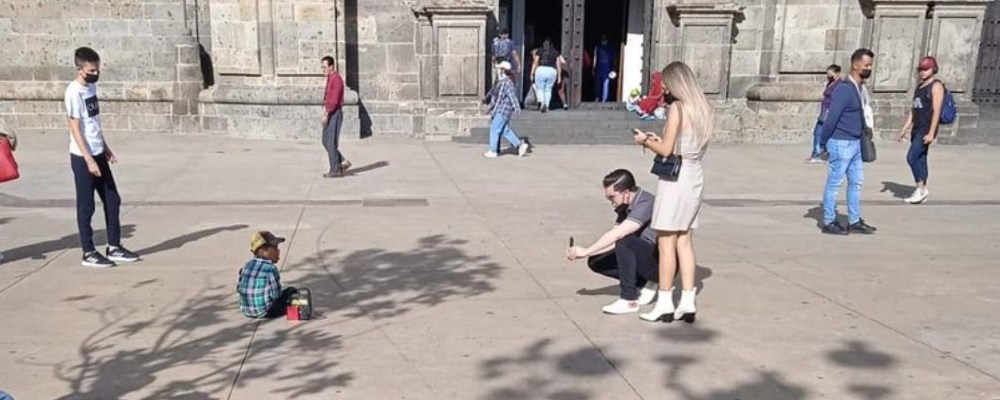Indigna pareja de turistas que le tomó fotos a un niño que pedía dinero