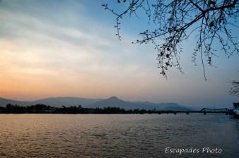Beau coucher de soleil sur la rivière de Kampot, le pont et les collines environnantes.