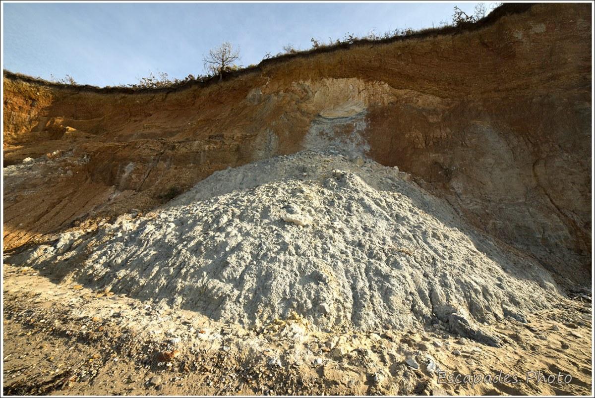 Un pan de falaise effondré et du sable argilo-calcaire gris-blanc