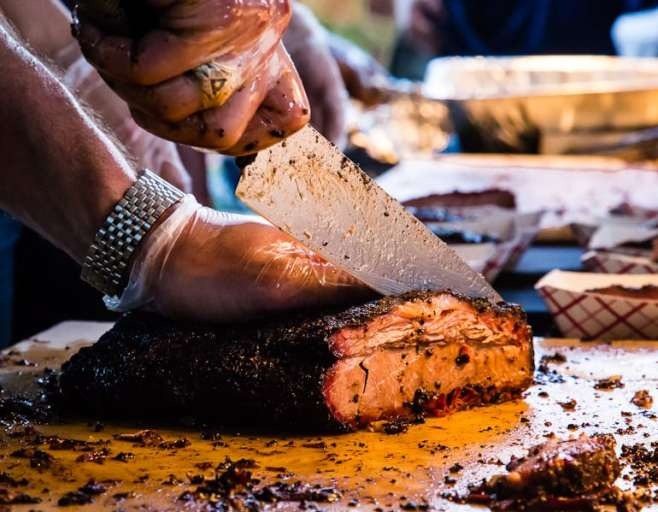 Justin Fourton carving a brisket