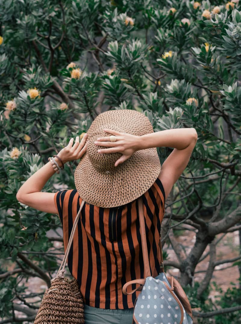 mujer caminando entre arboles de viaje