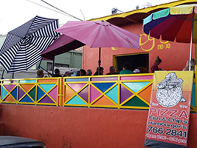 Patrons sitting on outdoor patio under multi coloured umbrellas at Perry's Pizza restaurant in Ajijic.