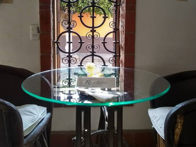 Glass table with reserved sign on it beside a wrought iron window looking out at the street at Teocintle Maiz restaurant in Ajijic.