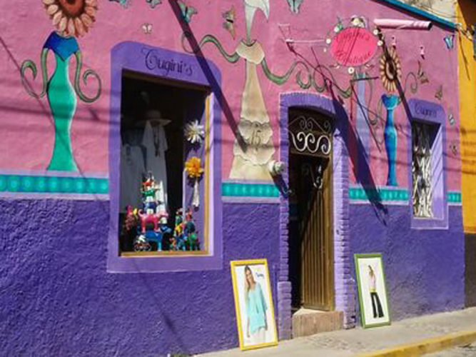 Pink and purple walls with whimsical drawings on wall of Cugini's Boutique in Ajijic