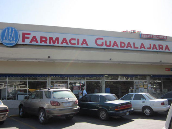 farmacia guadalajara storefront with red corporate lettering large open entranceway and cars parked out front