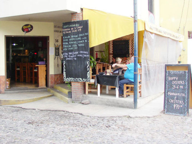Gossips, an Ajijic restaurant on the main road in ajijic showing large chaulkboard menu beside the outdoor dining area.