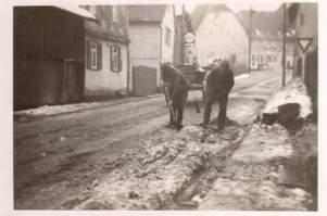 Deutsche Soldaten schaufeln Schnee, im Hintergrund links der Laden Mänscher/Knorr, 1940, Foto von R. Wick