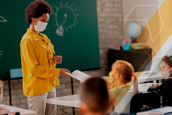 professora usando máscara dando aulas para alunos em sala de aula de forma presencial