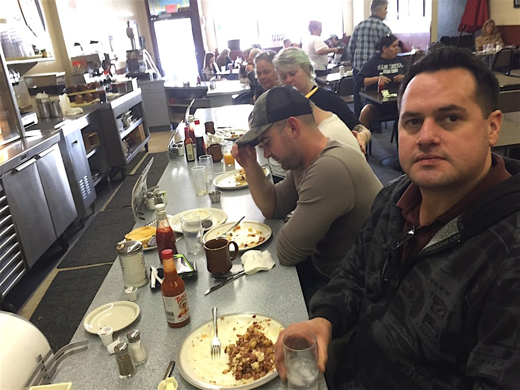 Escondido educational administrator Austin MacKay, corned beef hash on his plate, forefront said he brought cousin, and Escondido firefighter, Forrest Payne, left for last chance meals at Champion's.