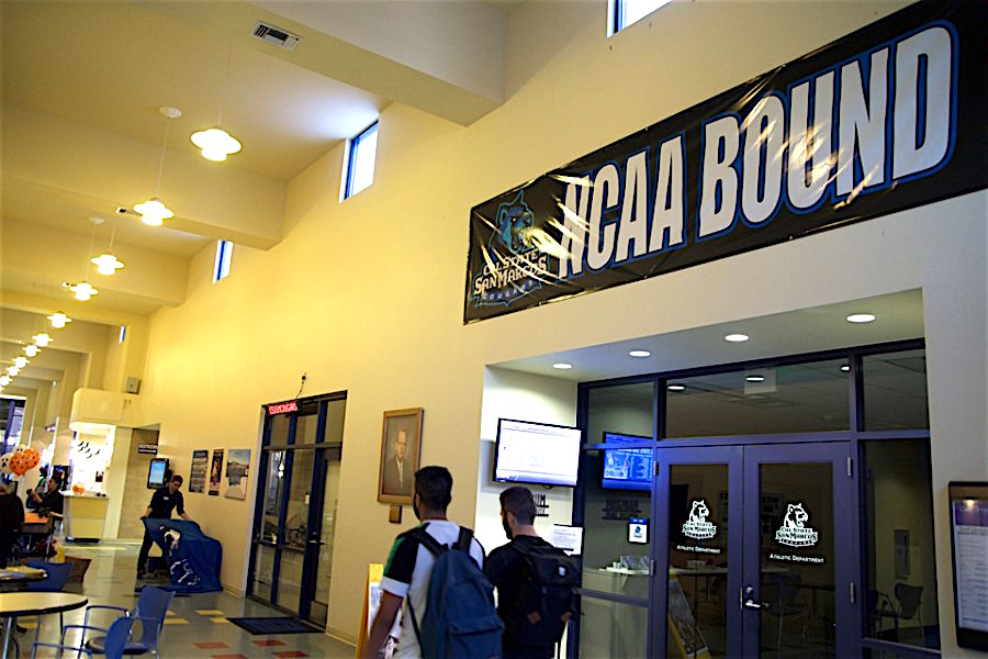 Students walk past a banner in the Clarke Field House on Oct. 30 marking California State University San Marcos' bid to be an NCAA school. (Photo by Troy Orem)