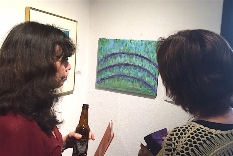 Patrons checking out Gladys Jimenez's abstract art work for auction.