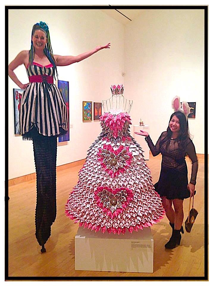 "Stilt-walker Jay Seven, left, with artist Erika San Luis Holly present Holly's ""Alice in wonderland""-inspired floral creation during a gallery preview party and fundraiser at the California Center for the arts, Escondido on May 20."