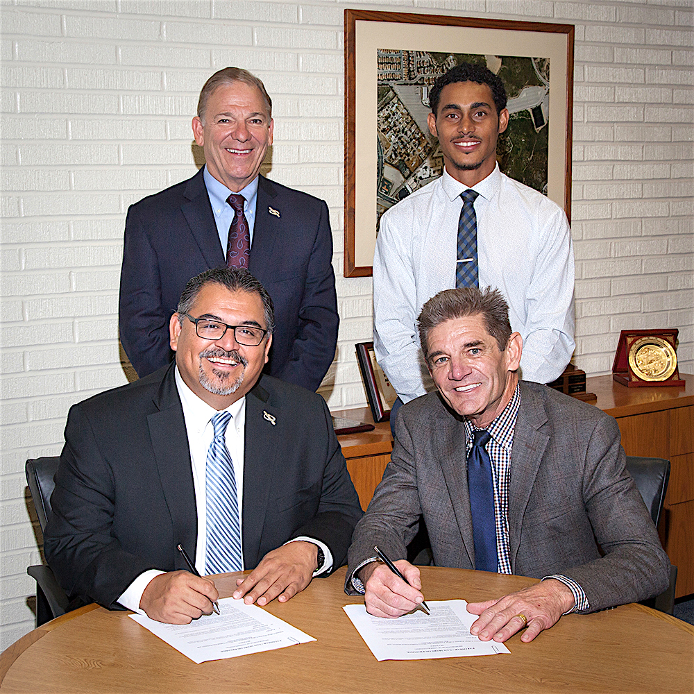 Officials from Palomar College and San Marcos Unified School District (SMUSD) are shown celebrating the establishment of The Palomar Promise, which will provide eligible SMSUSD graduates with free tuition while attending Palomar College. From left are (standing) Palomar College Foundation Executive Director Richard Talmo, Herbie Smith, Executive Director, San Marcos Promise, (sitting) Palomar College Interim Superintendent/President Adrian Gonzales and SMUSD Superintendent Dr. Kevin Holt.