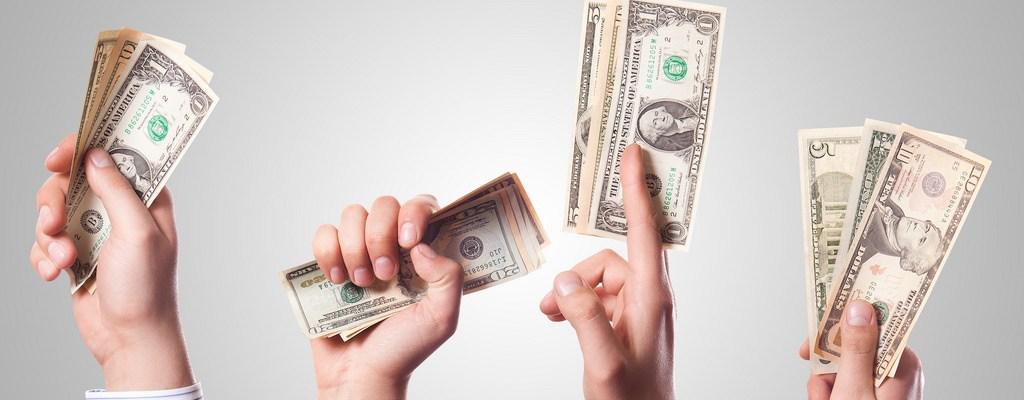 invertir en marketing. Foto de cuatro manos de 4 personas diferentes. Cada una de ellas sujeta un fajo de billetes.