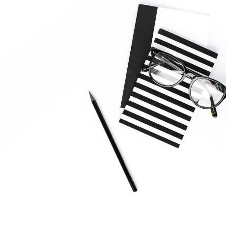 claves de Diseño Web - gafas y libreta de anotaciones blanco y negro