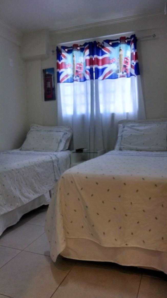 Quarto com camas de frente à TV a cabo. O apartamento pode ser organizado com camas de solteiro ou casal, dependendo da disponibilidade.