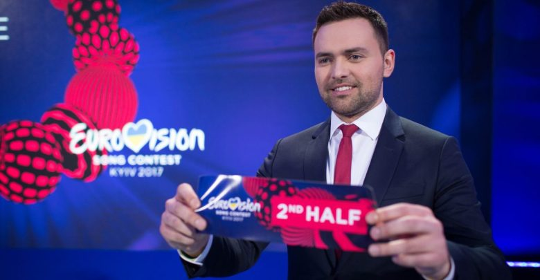 """Timur Miroshnychenko holding an allocation draw card declaring """"2nd half"""" for the Eurovision Song Contest 2017 held in Kyiv, Ukraine."""