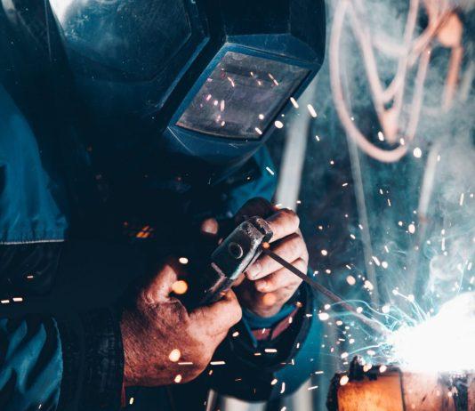Enfermedades laborales: Un soldador trabaja protegido por una máscara
