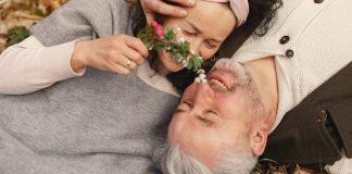 La vejez: una pareja mayor acostada en el césped y riendo