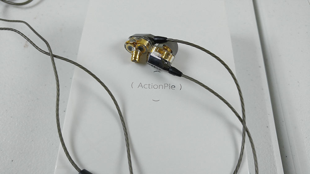 Picture of the ActionPie V1s earbuds layed out on top of it white product box
