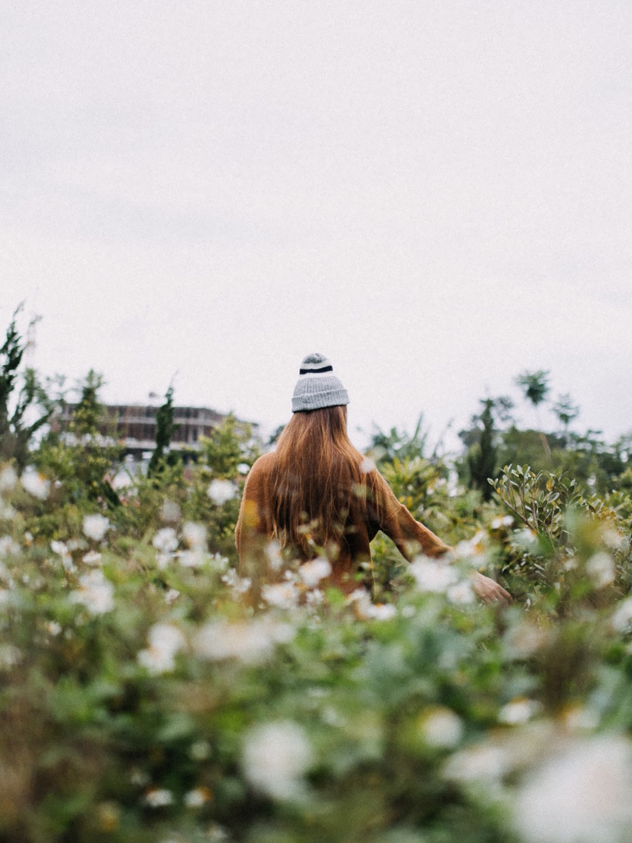 jeune femme rousse au style hispter avec un bonnet qui se promène dans un champ pour préparer les cultures de février