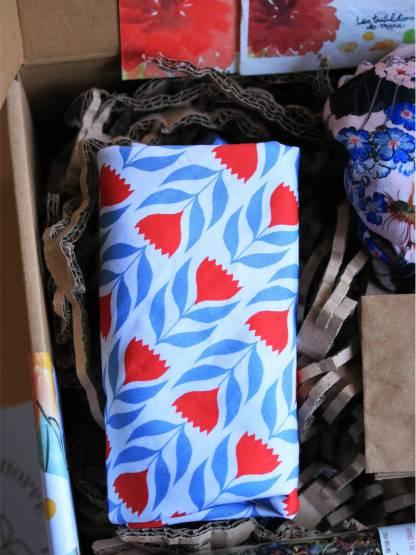 torchon essuie main au motif fleuri tulipe bleu et rouge sur fond blanc, plié en force de rectangle dans une box en carton