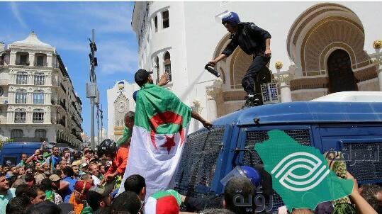 في الجزائر شرطي يواجه المتظاهرين بالغاز المسيل للدموع