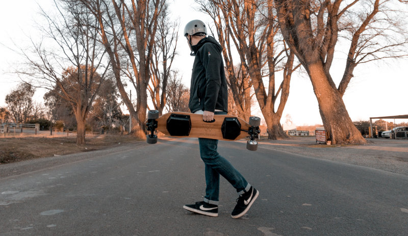 carrying electric skateboard across the road