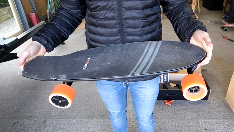 Holding the enSkate R3 Mini electric skateboard
