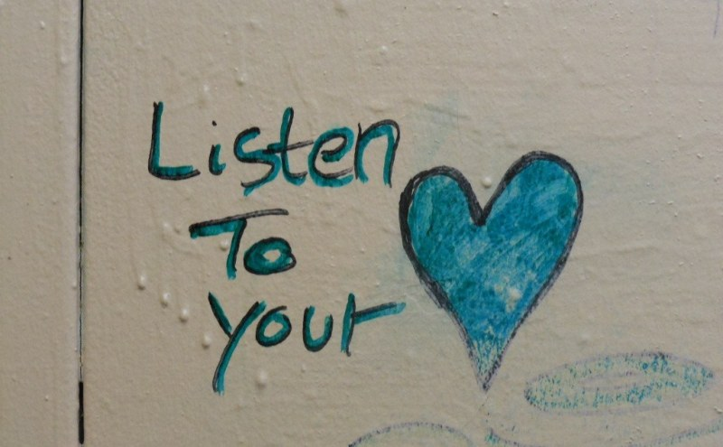 "graffiti on the wall, written ""listen to your heart"""
