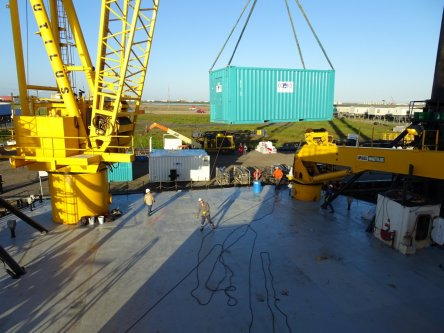 Using one of the L/B Myrtle's cranes to lift a containerised lab onto the deck.s