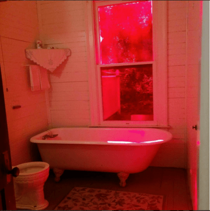 Peculiar red glass window treatment in the bath.