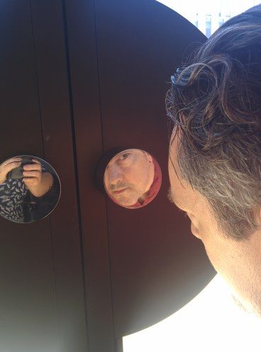 Architectural historian Nathan Marsak checks for bugs in a reflective door pull in the Peirera corporate HQ