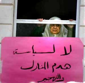 Palestinian woman looking trough the window