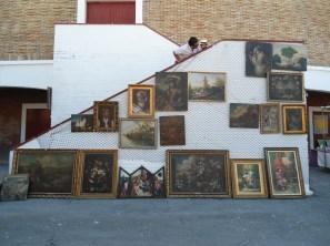 Exposición y venta de cuadros contra la escalera