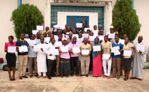 """El Segundo Retiro Interconfesional de Líderes Jóvenes en el Estado de Kaduna. Los participantes sostienen las pancartas que dicen: """"Seamos Musulmanes o Cristianos, somos Una Familia Bajo Dios."""""""