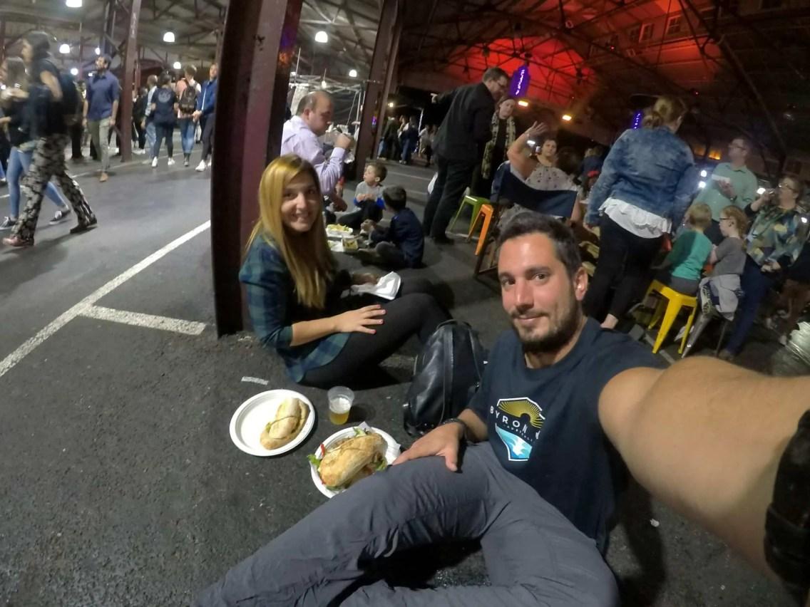 pareja comiendo en el piso en queen victoria market