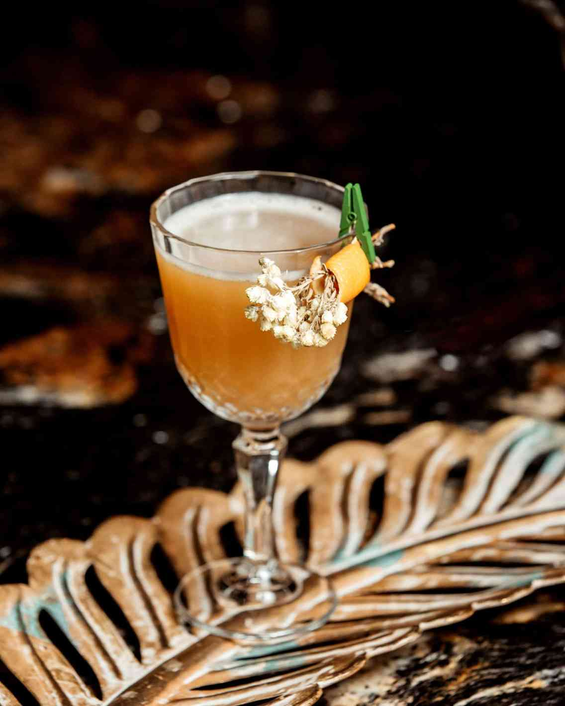 a crystal glass of cocktail garnished with flower and orange zest